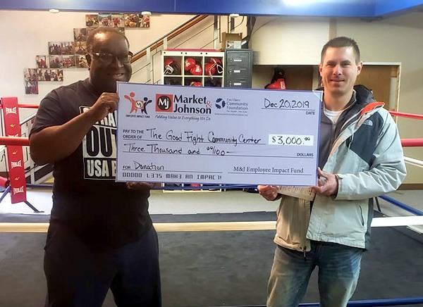 Nate at The Good Fight Community Center receiving a check for $3,000